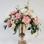 Soft pink and white flowers in a gold vase